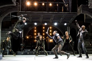 (foreground with swords, from left) Jeremy Woodard as Tybalt and Brandon Gill as Benvolio with the cast of THE LAST GOODBYE at The Old Globe.