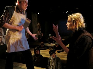 Zachary Baker-Salmon and Katherine Keberlein (with ensemble in the background) in Oracle's THE MOTHER. Photo by Ben Fuchsen.
