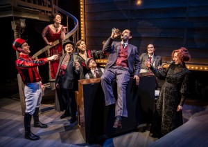 Andrew Rothenberg (drinking) and ensemble in Chicago Shakespeare Theater's production of ROAD SHOW, directed by Gary Griffin.