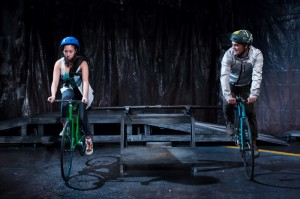 Aurora Adachi-Winter as Ora and Ricky Staffieri as  Eddie ride along the streets of Chicago in Buzz22 Chicago's Professional World Premiere of  Ghost Bike by Laura Jacqmin, directed by Company Member Sara Sawicki.