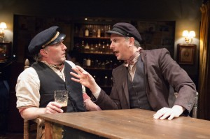 """""""Captain"""" Jack Boyle (Ron Rains, left) and his friend """"Joxer"""" Daly (James Houton) argue their days away at the pub rather than spending them at work in TimeLine Theatre's Chicago premiere production of the musical JUNO, book by Joseph Stein, music and lyrics by Marc Blitzstein, based on the play Juno and the Paycock by Sean O'Casey, directed by Nick Bowling with music direction by Doug Peck and Elizabeth Doran, presented at TimeLine Theatre, 615 W. Wellington Ave., Chicago, April 23 - July 27, 2014."""