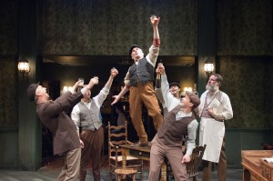"""""""Captain"""" Jack Boyle (Ron Rains, standing on table center) is declared a """"Daarlin' Man"""" by his friends at the pub (pictured from left: James Houton, Michael Reckling, Peter Sipla, Matthew Keffer and Andy Robinson) in TimeLine Theatre's Chicago premiere production of the musical JUNO, book by Joseph Stein, music and lyrics by Marc Blitzstein, based on the play Juno and the Paycock by Sean O'Casey, directed by Nick Bowling with music direction by Doug Peck and Elizabeth Doran, presented at TimeLine Theatre, 615 W. Wellington Ave., Chicago, April 23 - July 27, 2014."""