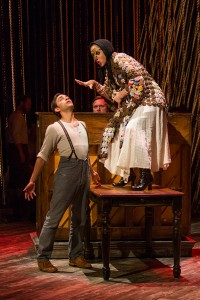 Ben Steinfeld as Baker and Alison Cimmet as Witch with (background) Andy Grotelueschen and Matt Castle in Stephen Sondheim and James Lapine's Into the Woods, in a reimagining by Fiasco Theater, directed by Noah Brody and Ben Steinfeld, in a production that originated at McCarter Theatre Center. Into the Woods runs July 12 - Aug. 17, 2014 at The Old Globe. Photo by Jim Cox.