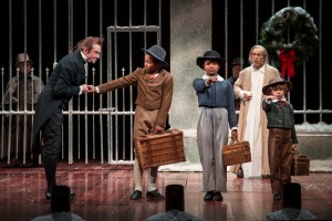 Larry Neumann Jr. (Schoolmaster), Phillip Cusic (Peter Cratchit), Skye Sparks (Belinda Cratchit), Larry Yando (Ebenezer Scrooge) and Nathaniel Buescher (Tiny Tim) in Goodman Theatre's A CHRISTMAS CAROL. Photo by Liz Lauren.
