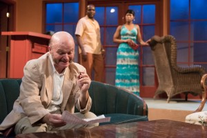 "Mr. Blake (Zach Bloomfield) finishes a crossword puzzle in the lobby of the Imperial Hotel before introducing himself to the newly arrived Americans David and Sarah Bradley (Robert Hardaway and AnJi White), in Eclipse Theatre's production of ""Mud, River, Stone"" by Lynn Nottage, directed by Andrea J. Dymond."