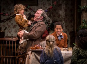 Nathaniel Buescher (Tiny Tim), Ron Rains (Bob Cratchit) and Phillip Cusic (Peter Cratchit) in Goodman Theatre's A CHRISTMAS CAROL. Photo by Liz Lauren.