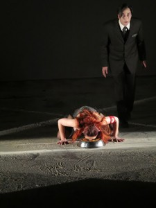 Daniel Damuzi as K witnesses Prostitute (Maria Bosque) transforming into an animal eating cat food, reminiscent of Kafka's Metamorphosis. Photo by Rosalie Baijer.