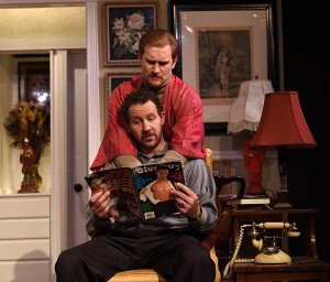 Stephen (Joe McCauley) and Mendy (JP Pierson) kill time with a magazine in Eclipse Theatre's THE LISBON TRAVIATA. Photo by Scott Dray.
