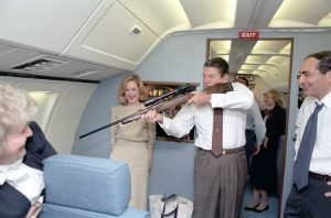 11/23/1983 President pointing a rifle out a window while flying aboard Air Force One during trip to California