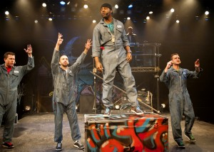 Jackson Doran, JQ and GQ throw their hands up as Postell Pringle (Othello) raps in Chicago Shakespeare Theater's production of Othello: The Remix, written, directed and composed by The Q Brothers.